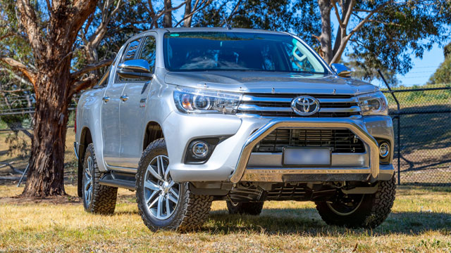 Silver Hilux ute on grass with blurred number plate