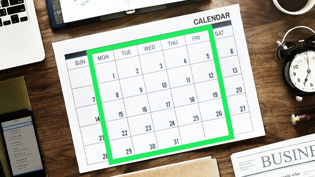 green bow outlining mid week dates on a calendar. Placed on a wood desk